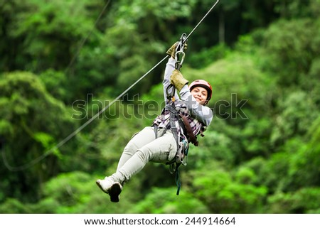 ADULT TOURIST WEARING CASUAL CLOTHING ON ZIP LINE TRIP, SELECTIVE FOCUS AGAINST BLURRED FOREST