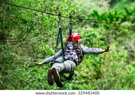 Adult Tourist Wearing Casual Clothing On Zip Line Trip Selective Focus Against Blurred Forest - stock photo