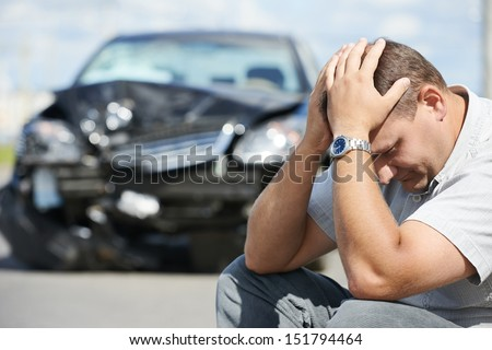 Adult upset driver man in front of automobile crash car collision accident in city road - stock photo