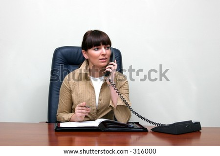 Adult white happy female in a white and roomy office talking on the phone and sitting behind a big brown desk .