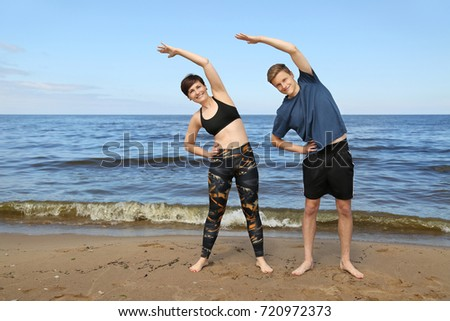 Adult woman and boy in sport wear do fitness exercises on beach on blue sea background - mother and son fitness