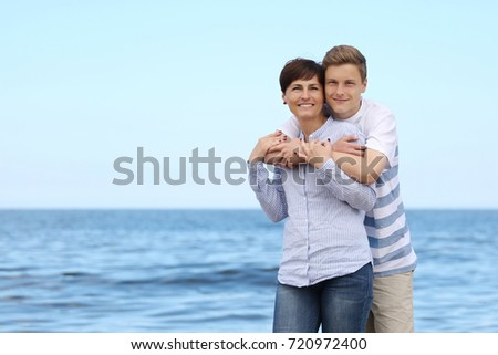 Adult woman and boy stand hugging on blue sea background - happy mother and son on vacations