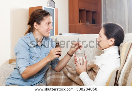 Adult woman caring for unwell mature mother in living room. - stock photo