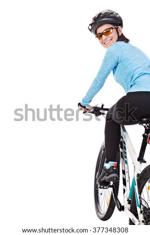 Adult woman cyclist riding a bicycle looks back and smiling isolated on white background. Studio shot. - stock photo