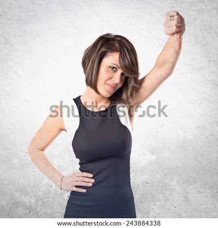 Adult woman doing a bad signal over textured background  - stock photo