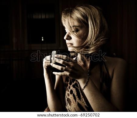 Adult woman drinking coffee in dark room beauty portrait - stock photo