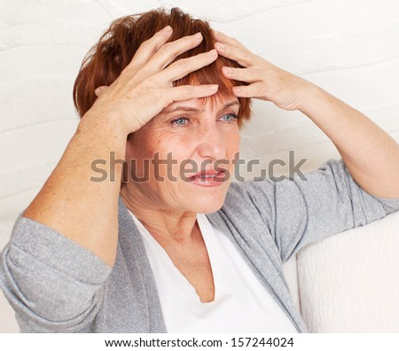 Adult woman has a headache. Sad mature female