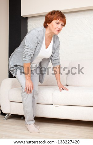 Adult woman has pain in the knee. Mature female at home - stock photo