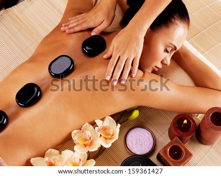 Adult woman having hot stone massage in spa salon. Beauty treatment concept.