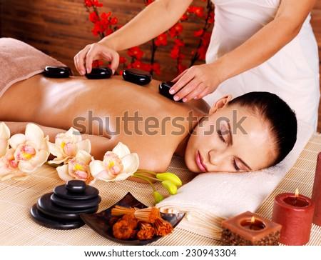 Adult woman having hot stone massage in spa salon. Beauty treatment concept. - stock photo