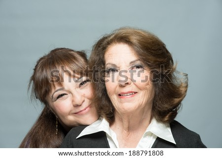 Adult woman hugging her  mature mom - stock photo