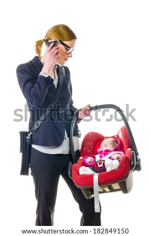 Adult woman in dark blazer sets her newborn daughter in a car safety seat, isolated against a white background. - stock photo