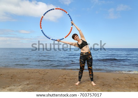 Adult woman in fitness wear with hula hoop in raised hands on beach on blue sea background