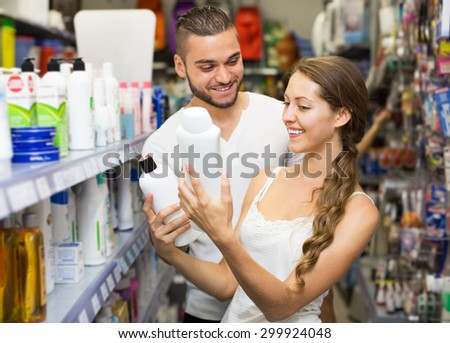 Adult woman in good spirits selecting shampoo at a store  - stock photo