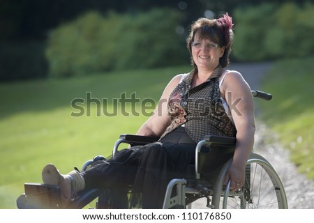 adult woman in wheelchair outdoors in the park