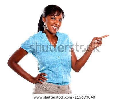 Adult woman looking at you and pointing to left on blue shirt against white background - copyspace - stock photo