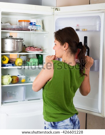 Adult woman looking for eat in refrigerator at domestic kitchen - stock photo