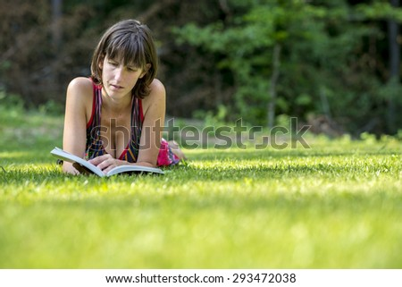 Adult Woman Lying on her Stomach on the Grassy Ground While Reading her Favorite Novel Book Seriously. - stock photo