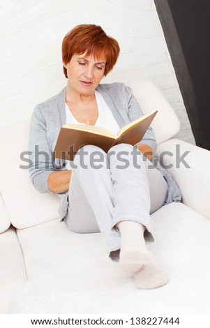 Adult woman reading book at sofa. Mature female at home