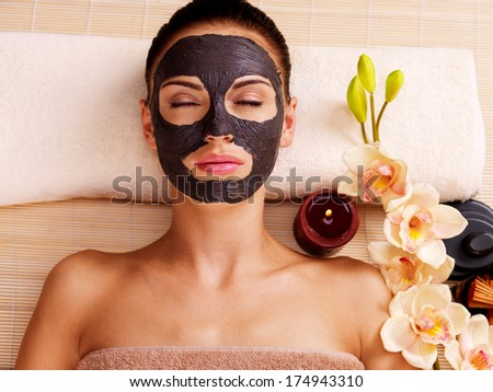 Adult woman relaxing in spa salon. Female face with cosmetic mask. Beauty treatment - stock photo