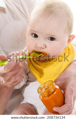 Adult woman sitting on a white chair and holds the 6 months old baby in her arms and lined with a yellow plastic spoon an orange carrot, isolated against white background. - stock photo