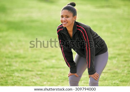 Adult woman wearing a black jacket resting with her hands on her knees while smiling optimistically at the camera