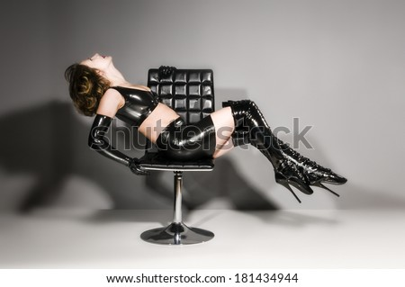 Adult woman wearing black shiny latex dress and overknee boots with extreme ballet heels. - stock photo