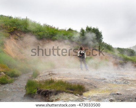 Adult woman with a backpack standing in a smoking crater of the volcano Mutnovsky on Kamchatka in Russia against the background of a hill with trees and sky with clouds