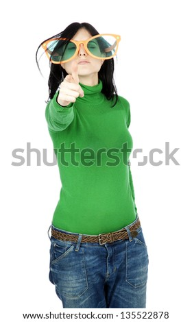 Adult woman with casual clothing and funky over sized orange spectacles, making a gun gesture with her hand and an aiming expression on her face, towards the camera. Isolated on white background. - stock photo
