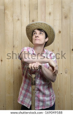 adult woman with cowboy hat leaning against a wooden wall
