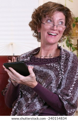 Adult woman with glasses and scarf thinking, relaxing and using a tablet