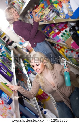 Adult women in good spirits selecting detergents in the store - stock photo