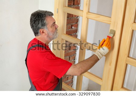 Adult worker painting new wooden door with paintbrush - stock photo