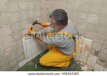 Adult worker remove, demolish old tiles in a bathroom with hammer and chisel