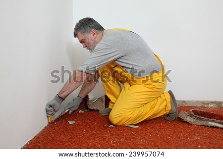 Adult worker removing old carpet in room - stock photo