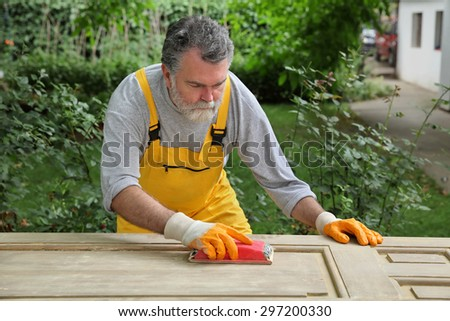 Adult worker sanding vintage wooden door with sanding block - stock photo