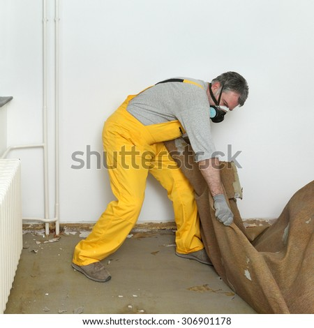 Adult worker with protective mask removing old carpet in room - stock photo