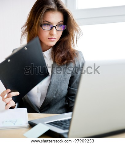 Adult young pretty business woman working at her office. She is very busy and hot.
