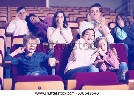 Adults and children enjoying scary film in cinema house