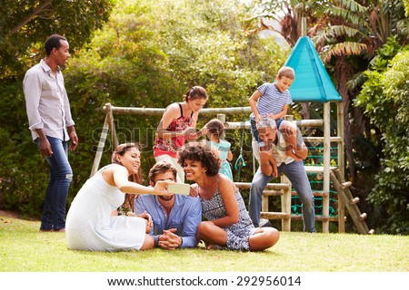 Adults and kids having fun in a garden - stock photo
