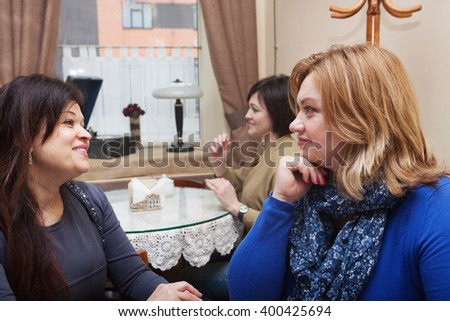 Adults girlfriend communicate  in a small  retro cafe