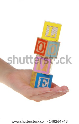 Adults hands hold children's blocks with the word love on a white background