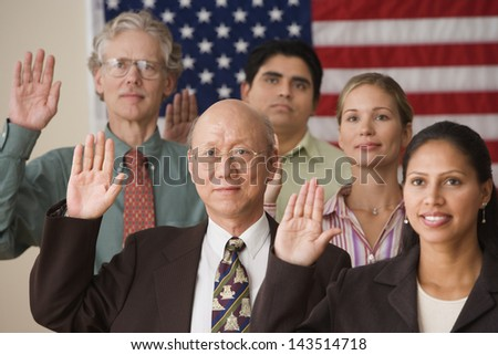 Adults raising their right hands before American flag - stock photo