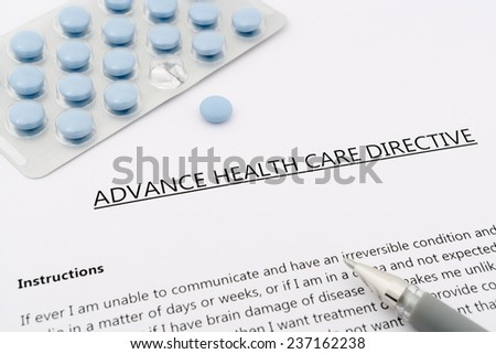 advance health care directive with blue pills ans grey pen - stock photo