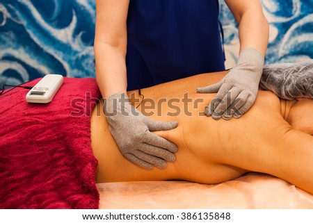 Advanced medical therapy with device for treating pain in muscles for female in Spa Salon done by Beautician Specialist wearing gloves and giving massage - stock photo
