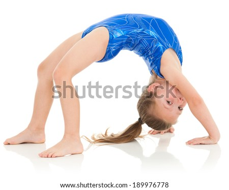 Advanced skill for a young girl, it's never too early to start kids in athletics! She is pushing up into a bridge position. She looks over and makes eye contact with the viewer. - stock photo