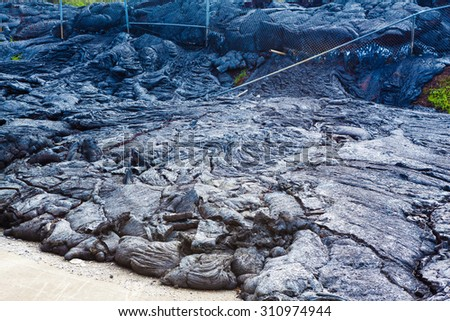 Advancing lava in the town of Pahoa melts and moves through a fence, Big Island, Hawaii - stock photo
