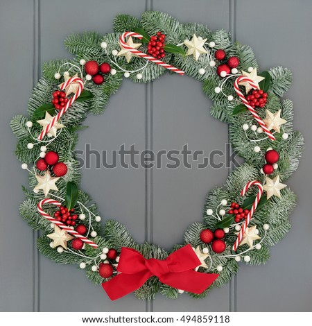 Advent and christmas wreath decoration with candy canes, red baubles, star decorations and holly and snow covered blue spruce fir over grey front door background.