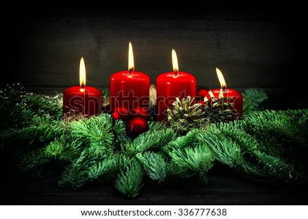 Advent decoration. Four red burning candles, ornaments and christmas tree branches. Vintage style toned picture - stock photo
