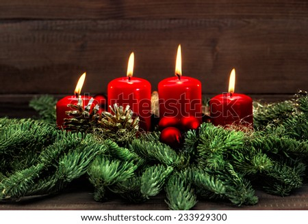 advent decoration with four red burning candles. holidays background. selective focus, vintage style toned picture - stock photo